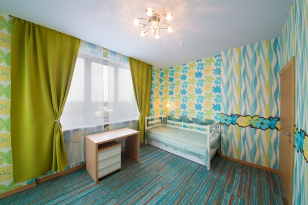 Beautiful modern childrens bedroom with carpet, curtains and chandelier.