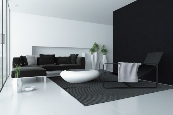 Minimalist grey and white modern living room interior with a black accent wall and floor to ceiling glass windows with a patio door and a trendy coffee table and recliner chair