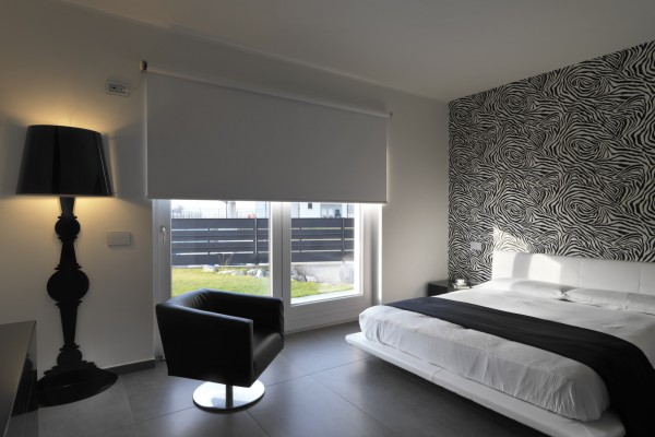 modern bedroom with leather armchair and black wall lamp